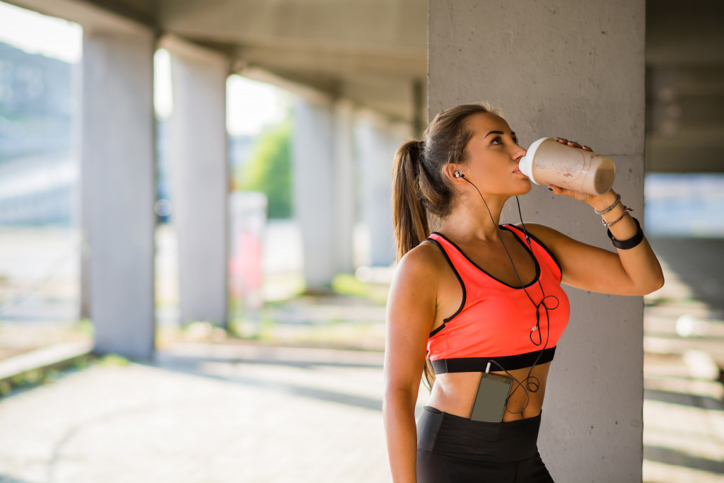 woman drinking after a run